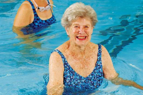 Older woman exercising in a pool.