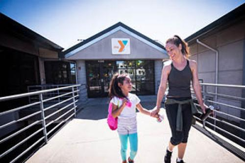 mother and daughter walking in from of the ymca after a great workout together