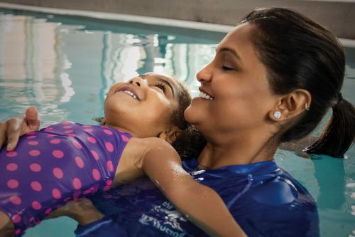 Swim instructor helping child swim