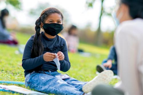 little girl wearing mask sitting outside doing an activity
