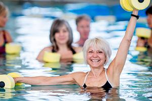 Member engaged in aqua zumba group fitness class in pool.