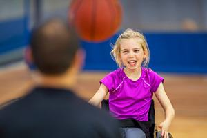 Special needs child playing with basketball.